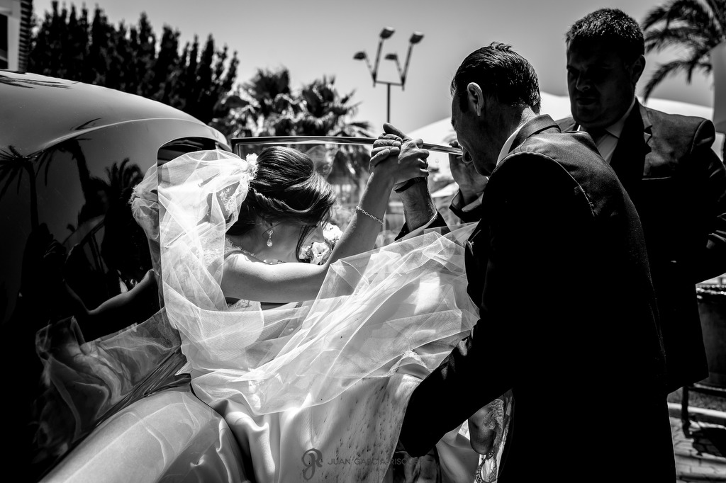 Novia saliendo de un coche clásico a la llegada del salón en Jaén