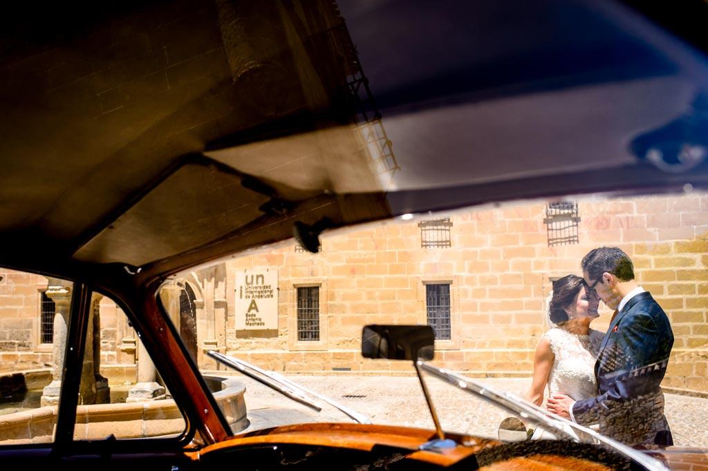 Novios besándose en un coche clásico