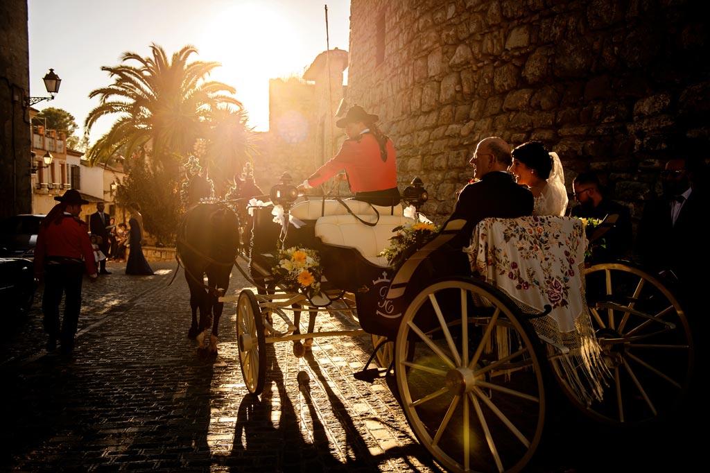 Novia llegando a la iglesia en coche de caballos acompañada del padrino para su boda
