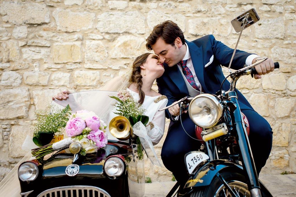 Novios felices besándose en una moto el día de su boda