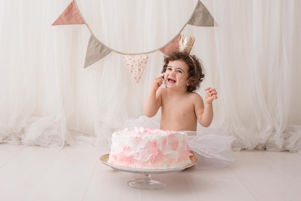 Bebé aplastando su pastel de cumpleaños en su sesión smash cake