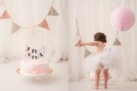 Bebé jugando con el pastel de cumpleaños en la sesión fotográfica de smash cake