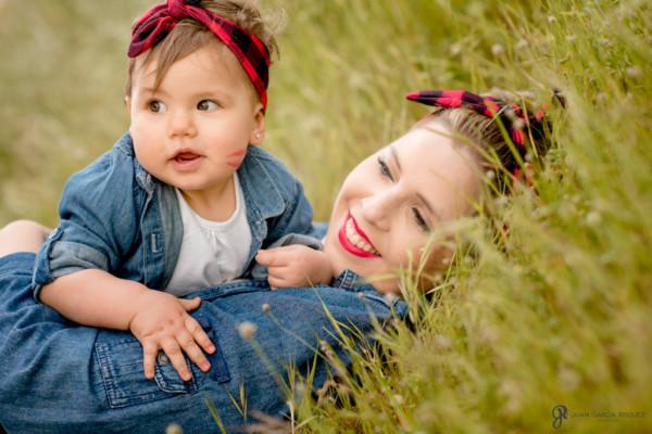 Foto de un bebé con su mamá tumbadas en un campo
