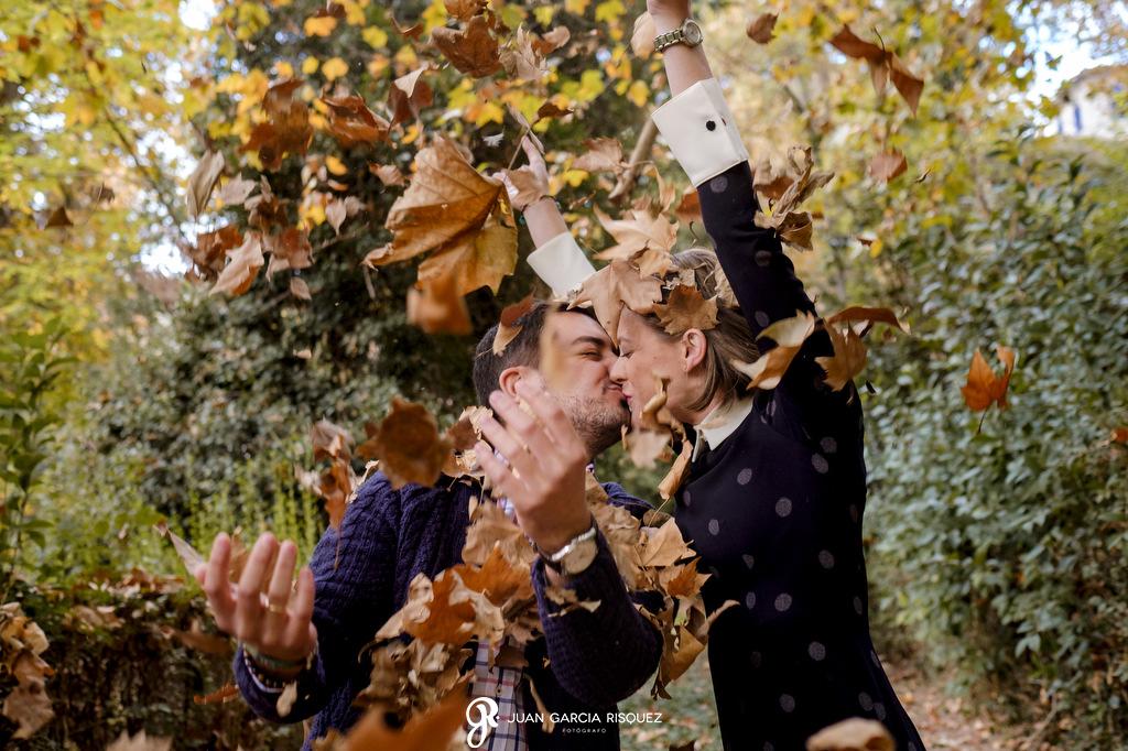 Novios jugando con hojas secas en su preboda