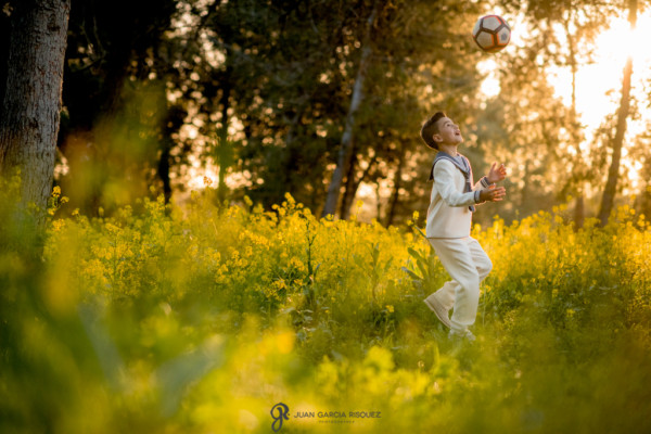 Niño jugando al balón vestido de marinero para las fotos de su Primera Comunión