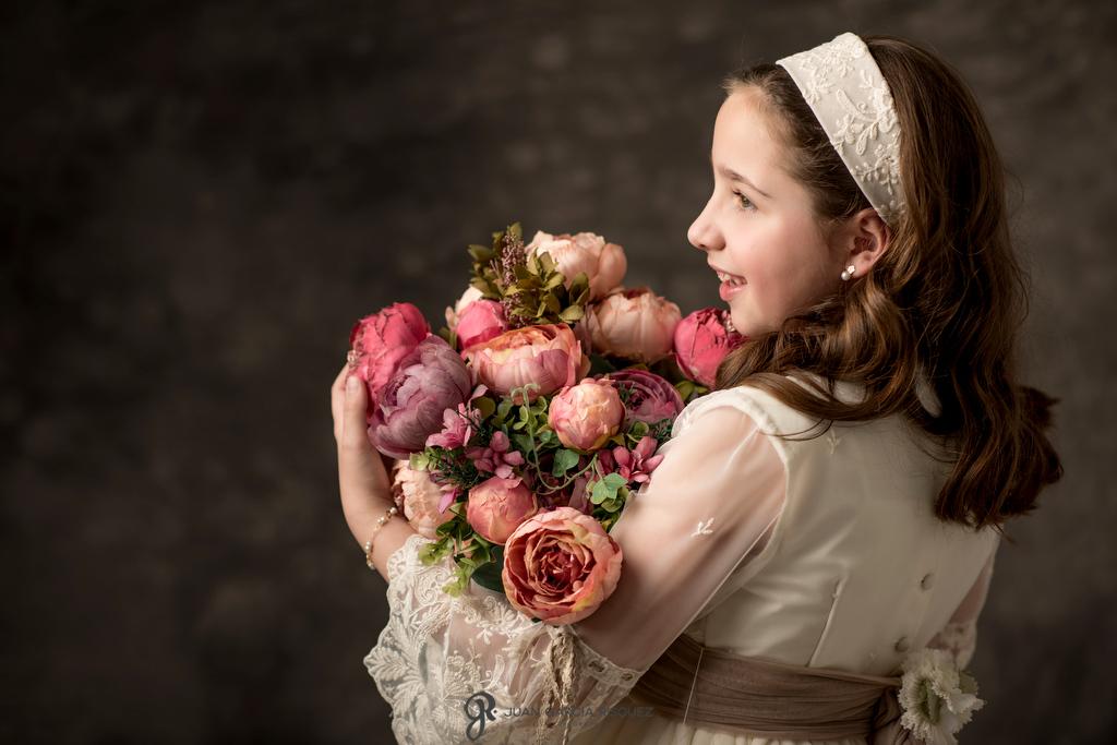 Fotos de una niña con flores en su reportaje de fotografías de Primera Comunión