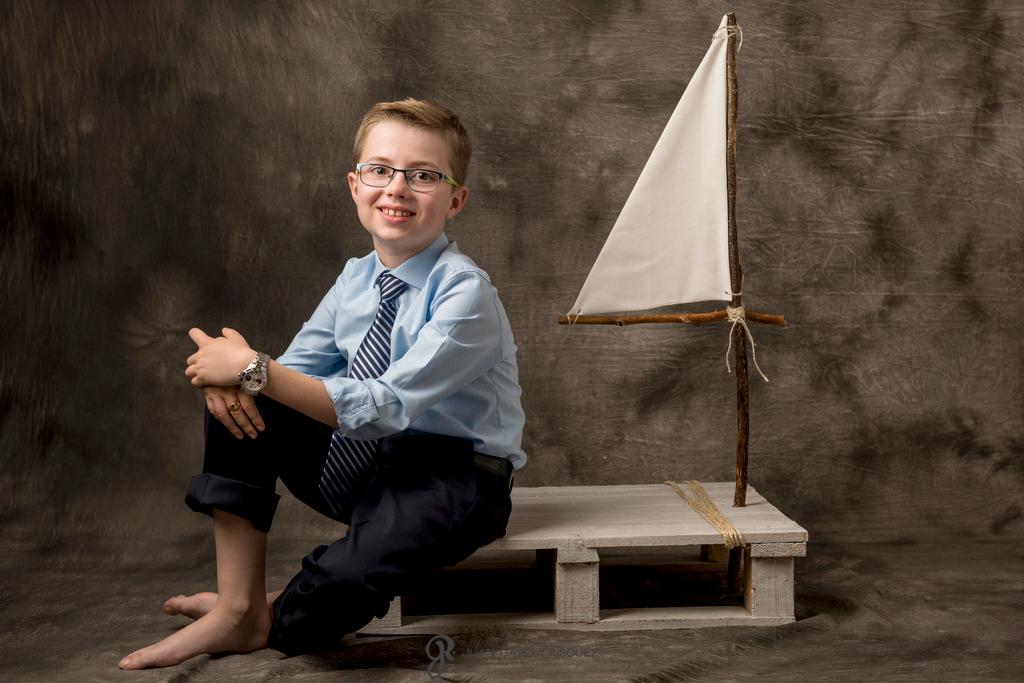 Niño sentado en un barco posando para sus fotos de Primera Comunión