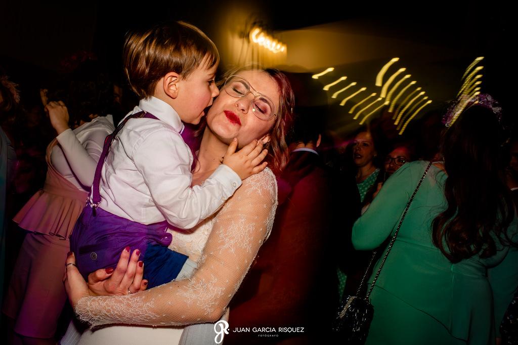 Novia bailando con un niño en su boda