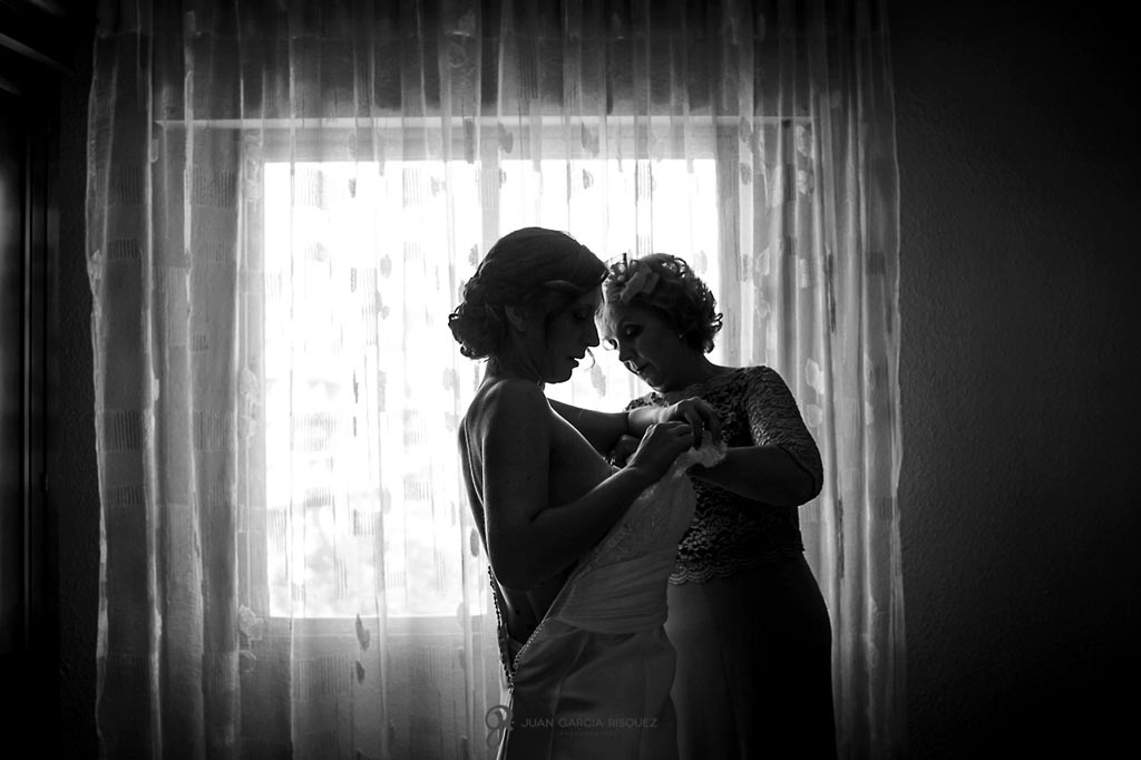 Reportaje de fotos de boda en Martos Jaen madre ayudando a vestirse a la novia